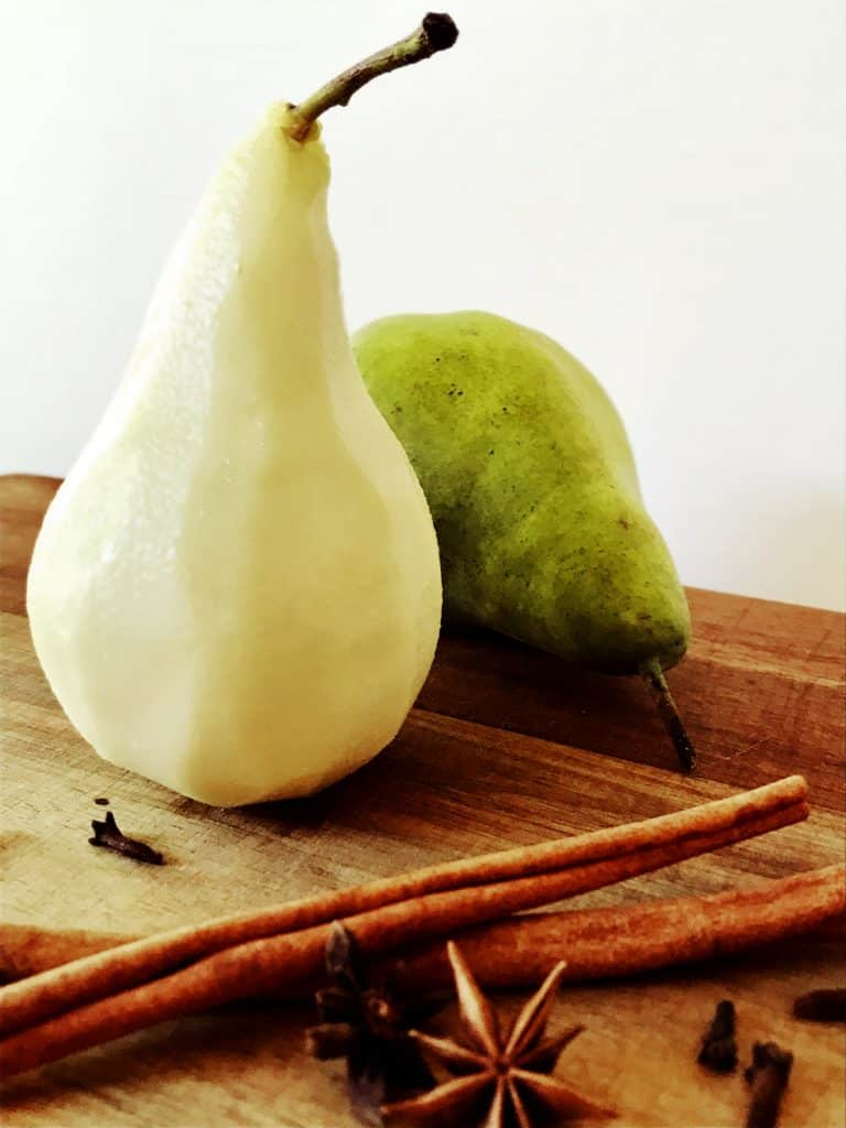 Preparing pears poached in red wine